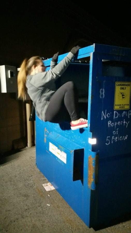 Junior Sarah Schaefer hops into a dumpster at 5 Below after dark.