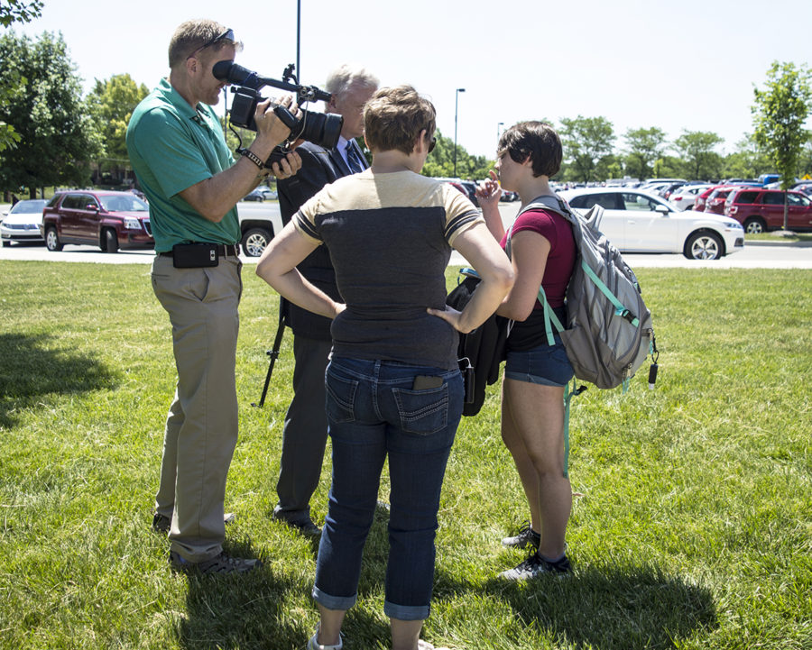 A news crew interviews a student and their family member as they leave the building.