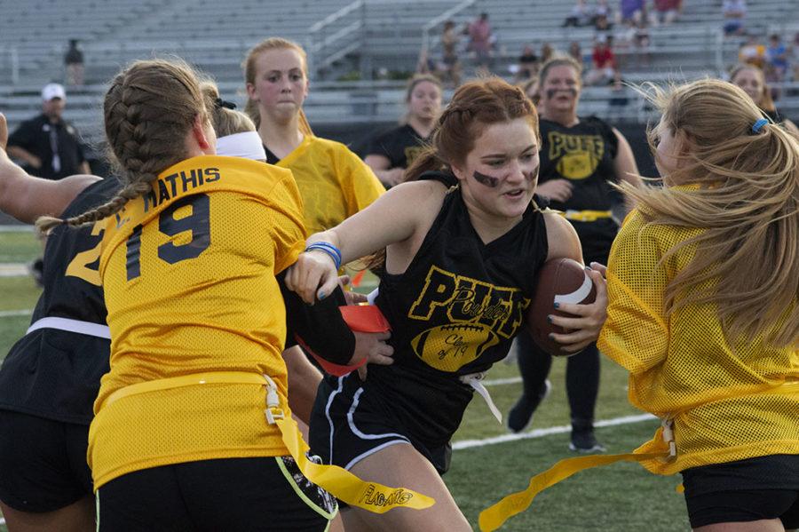 Senior Allison Santa Rita pushes past her opponents during the powderpuff game.