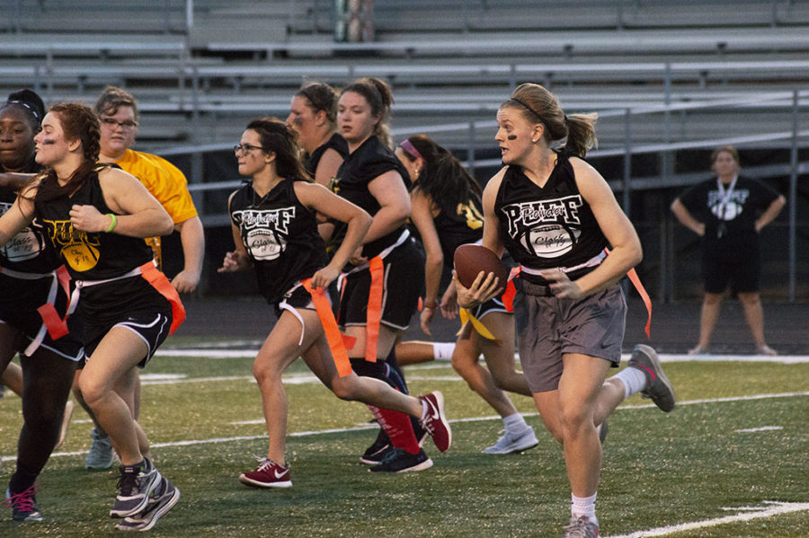 Senior Madison Whetro runs down the field with the ball beside her fellow teammates.
