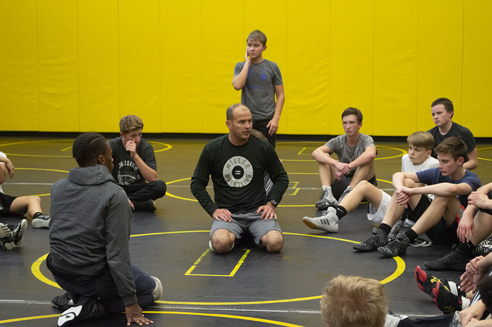 Coach Weimer dresses his team during a wrestling practice.