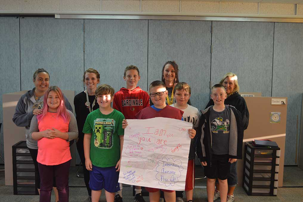 Griffin's class holds the poster for their friend Ian. The poster explains all the good things they think about him.