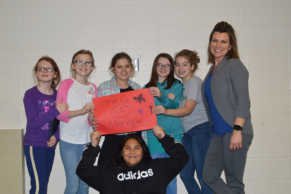 North elementary students smile joyously as they pose next to Melissa Jones, creator of the Girls Positivity Club. The girls proudly show off their colorful posters.