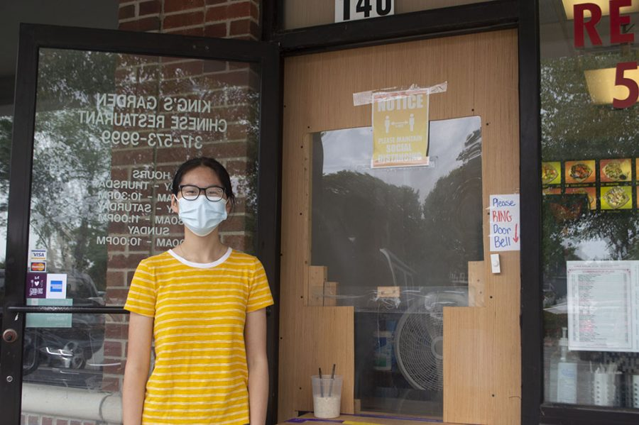 Nicole Liu stands in front of King's Garden. The door of the takeout restaurant has been altered to adhere to COVID precautions.