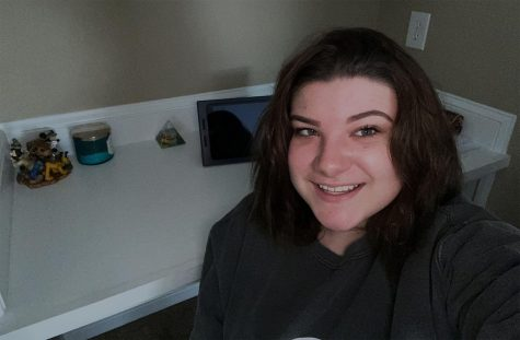 """Junior Chloe Hurst takes a picture by her at home workspace. She describes the online schedule as """"self paced""""."""