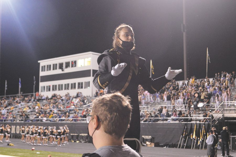 Oberhart directs the Marching Millers during a football game.