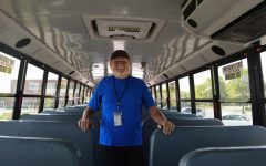 Bus driver Dworkus stands proudly inside his bus