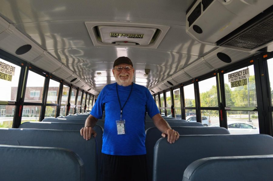 Bus driver Dworkus stand s proudly inside his bus